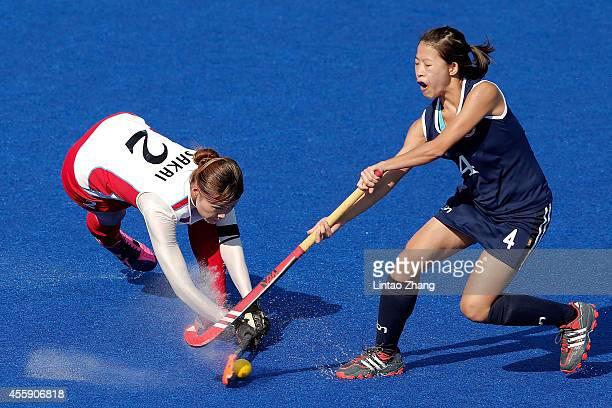 Shiho sakai of Japan handles the ball against Ka Ki Janet Ho of Hong Kong during the Hockey Women's Pool B match between Japan and Hong Kong during...