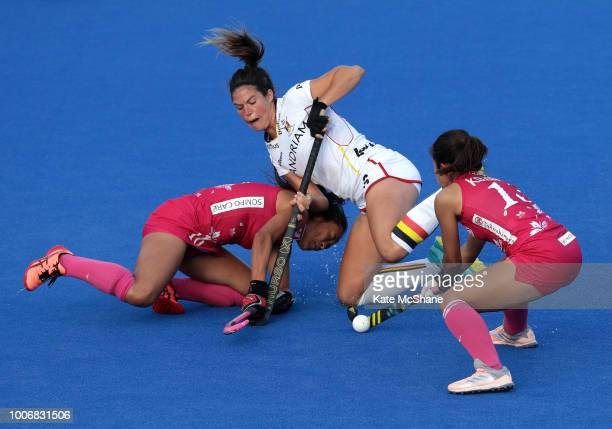 Shihori Oikawa and Miki Kozuka of Japan battle for possession with Anouk Raes of Belgium during the Pool D game between Japan and Belgium of the FIH...