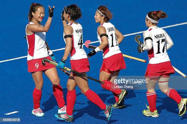 Shihori Oikawa is congratulated after scoring a goal with Kana Nomura and Akane Shibata of Japan during the Hockey Women's Pool B match between Japan...