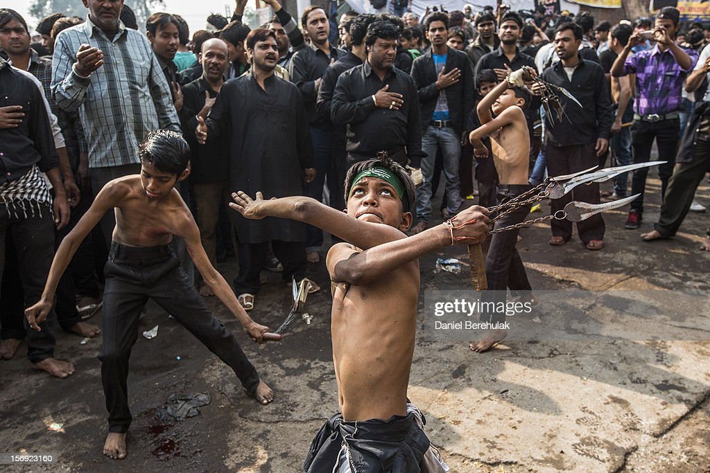 Shiite boys strike themselves with sharpened blades attached to chains as part of a self-flagellation ritual during a religious procession marking Ashura on November 25, 2012 in New Delhi, India. The religious festival of Ashura, which involves a ten-day mourning period starting with the first day of Muharram on the Islamic calendar, commemorates and mourns the seventh-century martyrdom of Prophet Muhammad's grandson Imam Hussein in the battle of Karbala.