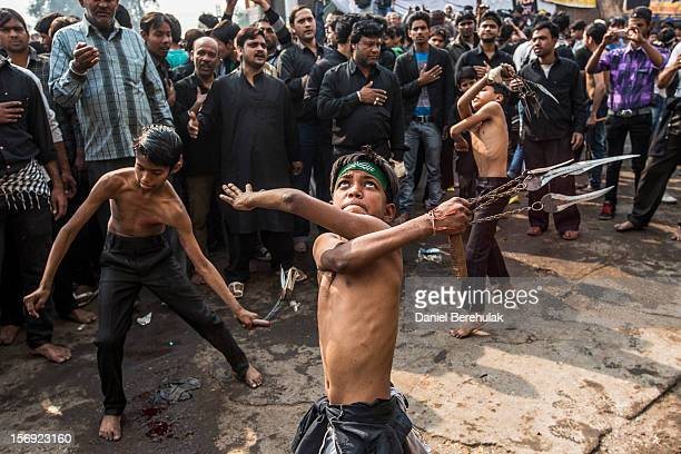 Shiite boys strike themselves with sharpened blades attached to chains as part of a selfflagellation ritual during a religious procession marking...