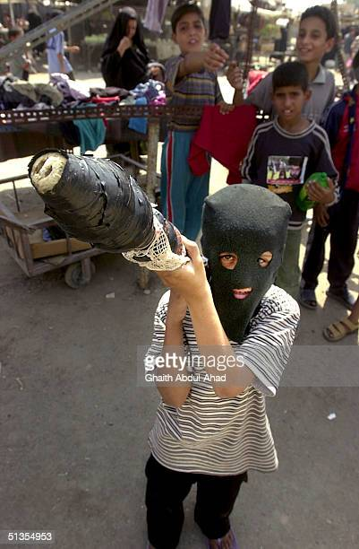Shiite boys wearing a ski mask brandishes a wooden stick made to look like an RPG launcher as thousands of Iraqi Shiites loyal to the radical cleric...