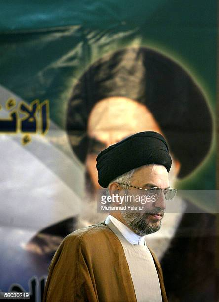 Shiite cleric Abdul-Aziz al-Hakim, head of the Supreme Council for the Islamic Revolution in Iraq , a main Shiite party, stands in front of a picture...
