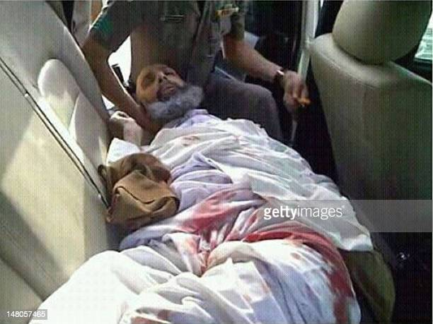 Shiite cleric and goverment critic Sheikh Nimr alNimr lies wounded in the back of a police car following his arrest on July 8 2012 Two protestors...