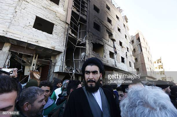 A Shiite cleric stands amid Syrian progovernment forces and residents at the site of suicide bombings in the area of a revered Shiite shrine in the...
