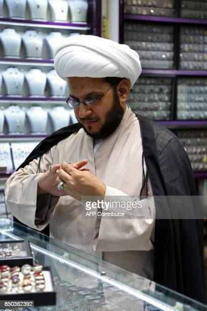 A Shiite cleric tries on a ring at a jewellery shop in the main market of Iraq's holy city of Najaf on September 13 2017 Strategically located facing...