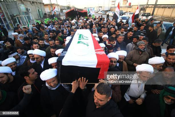 Shiite clerics and members of the Hashed alShaabi carry the coffin as they mourn the death of a religious member of their community Sheikh Mohannad...