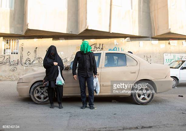 Shiite couple with veiled face in front of a car covered with mud decorated for Ashura commemoration Lorestan Province Khorramabad Iran on October 11...