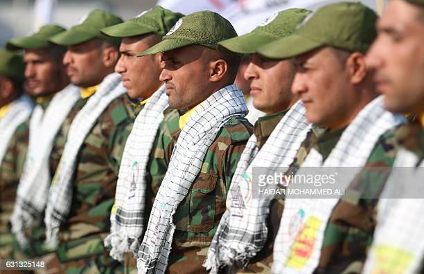 Shiite fighters from the Hashed alShaabi attend a ceremony to mark the 95th anniversary of the creation of the Iraqi police at the Shaabiyah training...