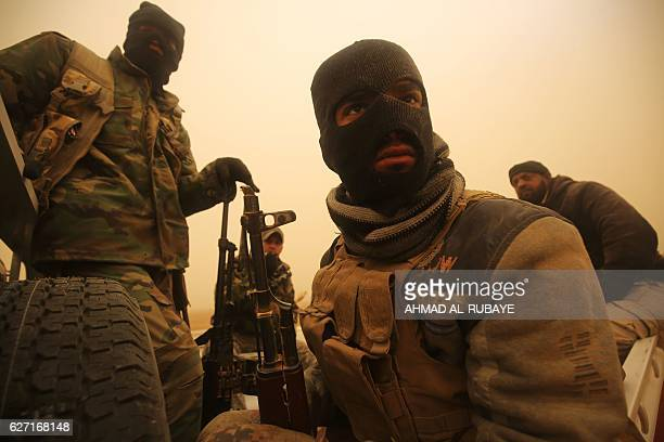 Shiite fighters from the Hashed al-Shaabi paramilitaries sit in a vehicle driving through a desert area near the village of Al-Boutha al-Sharqiyah,...