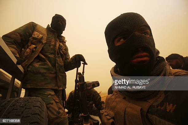 Shiite fighters from the Hashed alShaabi paramilitaries sit in a vehicle driving through a desert area near the village of AlBoutha alSharqiyah west...