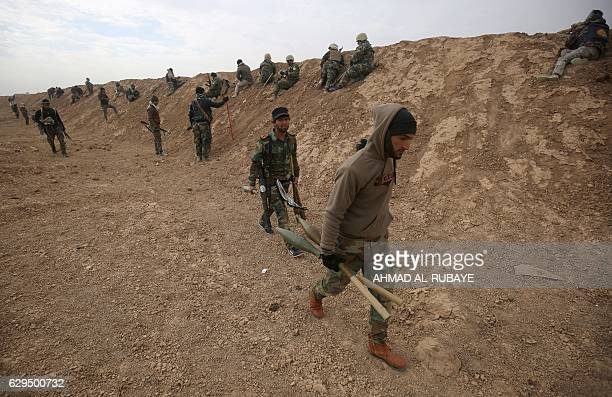 TOPSHOT Shiite fighters from the Hashed alShaabi paramilitary units advance towards the village of Shwah south of the city of Tal Afar west of Mosul...