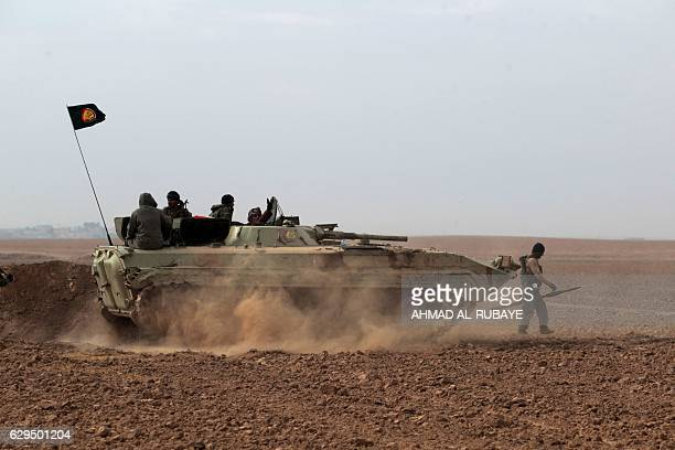 Shiite fighters from the Hashed alShaabi paramilitary units drive a tank as they advance towards the village of Shwah south of the city of Tal Afar...