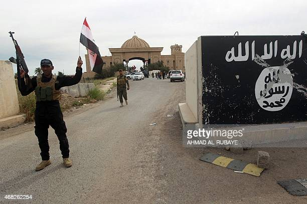 Shiite fighters from the Popular Mobilisation units pose in front of a mural depicting the emblem of the Islamic State group outside one of the...