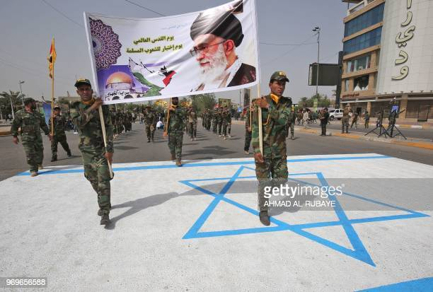 Shiite fighters of paramilitary units step on an Israeli flag drawing during a rally to mark Quds day a commemoration first initiated by Iran in 1979...