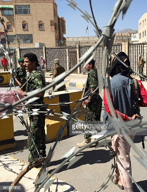 Shiite Huthi militiamen wearing uniforms confiscated from the Yemeni army stand at a barrier in the area around the house of the country's president...