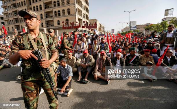 A Shiite Huthi rebel fighter stands guard as supporters wave flags and shout slogans during a rally in Sanaa commemorating the fourth anniversary of...