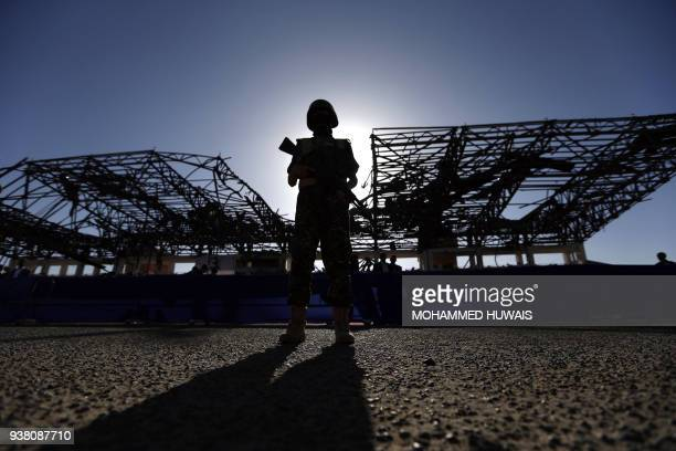 A Shiite Huthi rebel fighter stands guard during a rally marking the third anniversary of the Saudiled coalition's intervention in Yemen in the...