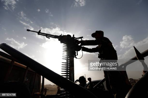 A Shiite Huthi rebel stands on a vehicle mounted with a machinegun during a gathering to mobilise more fighters to battlefronts to fight Yemeni...
