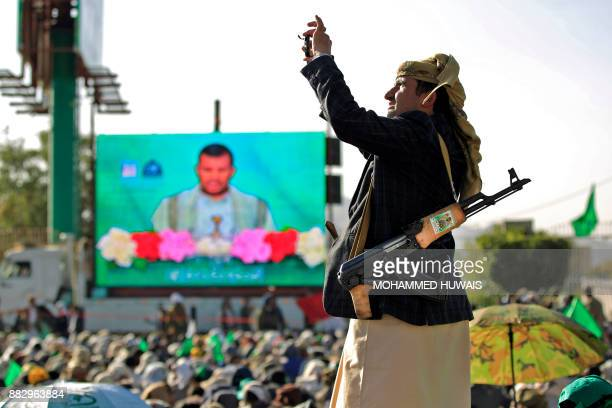 A Shiite Huthi rebel uses his cell phone to film as his comrades and their supporters watch on a big screen a live speech given by leader AbdulMalik...