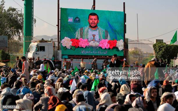 Shiite Huthi rebels and their supporters watch on a big screen a live speech given by leader AbdulMalik alHuthi as they attend a rally outside...