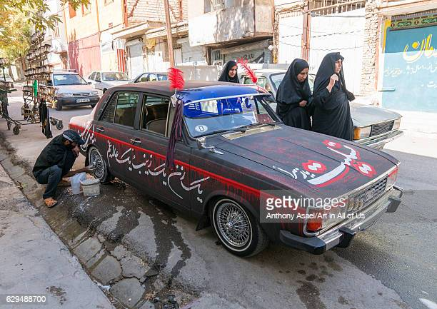 A shiite iramian man washes his car decorated for Ashura celebrations to commemorate the martyrdom anniversary of Hussein Lorestan Province...