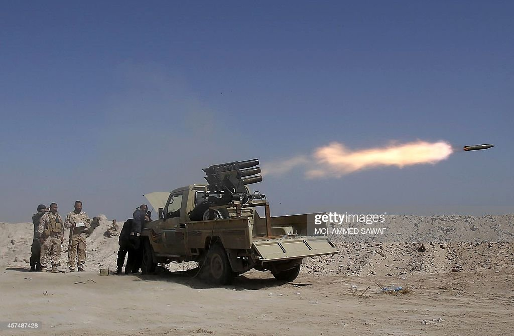Shiite Iraqi fighters, loyal to Grand Ayatollah Ali al-Sistani, fire missiles from a launcher during clashes with Islamic State militant group fighters in Jurf al-Sakher, north of the Shiite shrine city of Karbala on October 19, 2014.