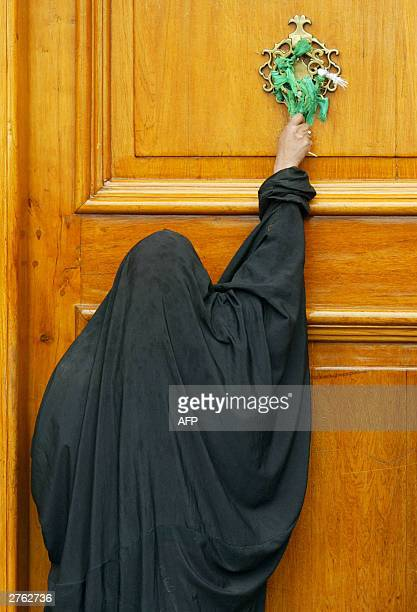 Shiite Iraqi woman touches a cloth tied to a knob on one of the entrance doors to the Imam Ali shrine in the holy city of Najaf 185 kms south of...