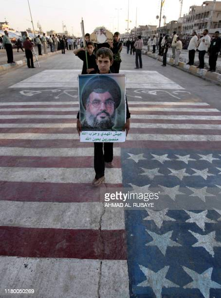 A Shiite Iraqi youth carries a picture of Lebanese militia Hezbollah Leader Hassan Nasrallah as he walks over the US national flag during a parade in...
