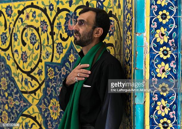 Shiite man praying in front of colorful faience tiles at Shrine of sultan Ali Kashan County Mashhade Ardahal Iran on October 10 2016 in Mashhade...
