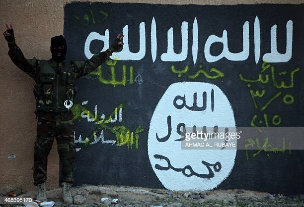 A Shiite member of the Iraqi progovernment forces flashes the Vsign for 'victory' as he stands in front of a mural depicting the Islamic State...