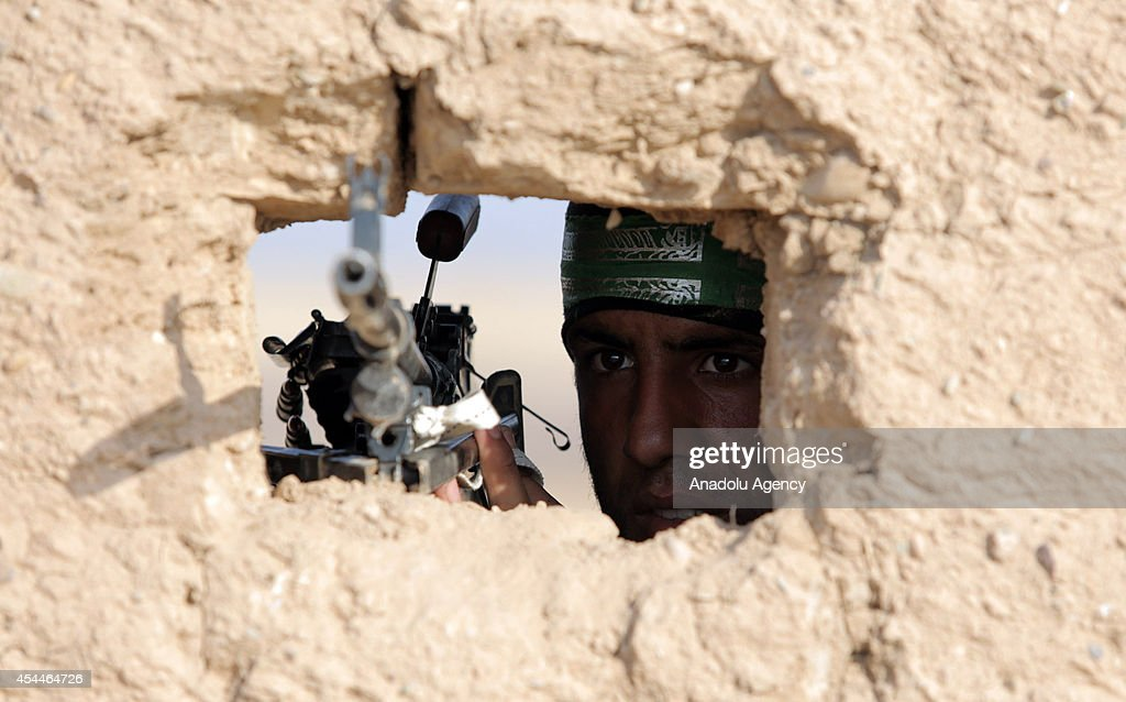 A Shiite militant aims behind a wall in Amirli after Iraqi forces have entered the northern town of Amirli which had been under the siege of Islamic State militants for over two months in Saladin ,Iraq on September 1, 2014. Supported by Kurdish forces and Shiite militias, the Iraqi army launched an offensive shortly after the U.S. carried out airstrikes against Islamic State (IS) positions near the town, and dropped aid for the nearly 20,000 Shiite Turkmen trapped in Amirli. The government forces and Kurdish peshmerga forces have been fighting against the militant group to block their advance.