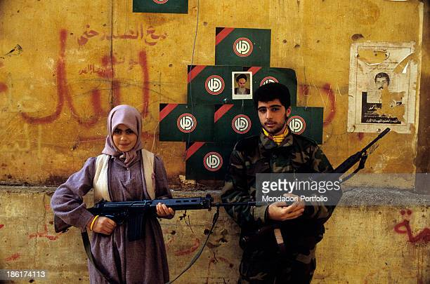 Shiite militiaman and young woman holding light machineguns in front of a poster depicting the portrait of Iranian ayatollah Ruhollah Khomeini...