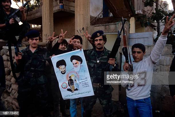 Shiite militiamen rejoicing and holding a poster depicting the portraits of Iranian ayatollah Ruhollah Khomeini and Lebanese Shiite spiritual and...
