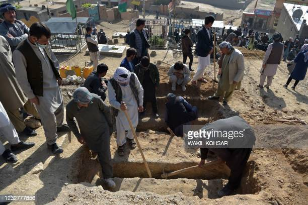 Shiite mourners and relatives dig graves for girls, who died in yesterday's multiple blasts outside a girls' school, during the burial at a desolate...