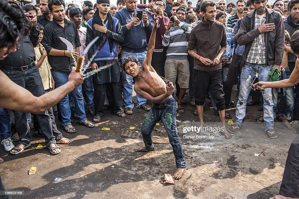 A Shiite muslim boy strikes himself with sharpened blades attached to chains as part of a self-flagellation ritual during a religious procession marking Ashura on November 25, 2012 in New Delhi, India. The religious festival of Ashura, which involves a ten-day mourning period starting with the first day of Muharram on the Islamic calendar, commemorates and mourns the seventh-century martyrdom of Prophet Muhammad's grandson Imam Hussein in the battle of Karbala.