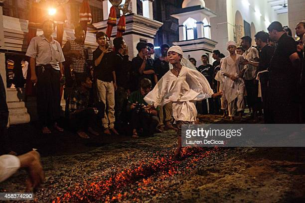 Shi'ite Muslim boys do a fire walk during the second night of Ashura a commemoration involving running over fiery coals to mourn the martyrdom of...