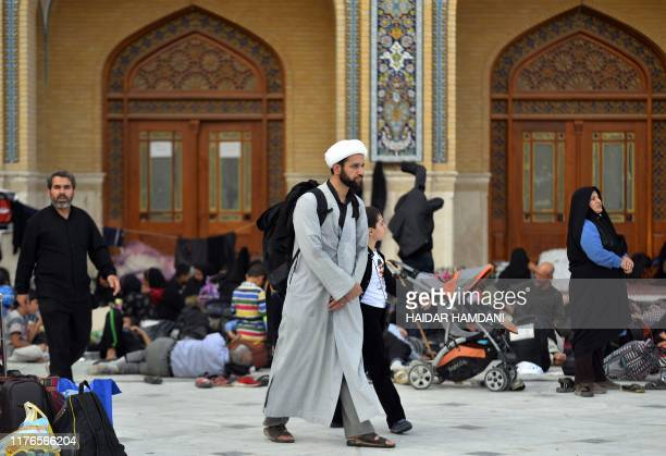 A Shiite Muslim cleric walks in a hall transformed into a temporary accomodation for pilgrims of modest means in the Imam Ali shrine in the holy...