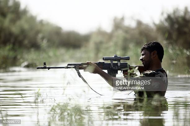 Shiite Muslim fighter, loyal to Iraqi Shiite cleric Moqtada al-Sadr, takes part in a last combat training near the city of Najaf on August 23 before...