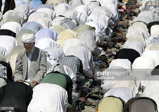 Shiite Muslim Iraqis perform the weekly Friday prayer at Imam Ali's shrine in Najaf 05 September 2003 one week after a massive car bomb killed...