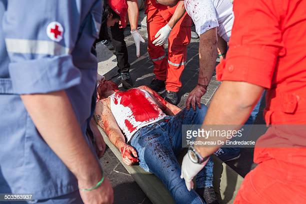 Shiite muslim man, covered in his own blood, being carried away on a stretcher by paramedics, after fainting due to excessive blood loss from...