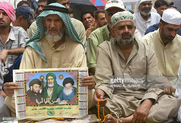 A Shiite Muslim man holds a poster with images of antiAmerican Shiite cleric Moqtada alSadr Imam Ali the cousin of the Prophet Mohammed and the...