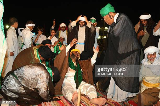 A Shiite Muslim man plays the roll of Ali ibn Abi Talib as he lies on the ground surrounded by his supporters during a play depicting his murder in...