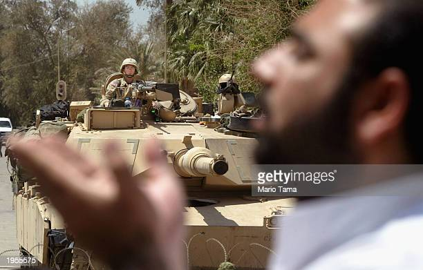 Shiite Muslim man prays in front of an American tank outside the Palestine Hotel April 28 2003 in Baghdad Iraq Several hundred Shiite Muslims...