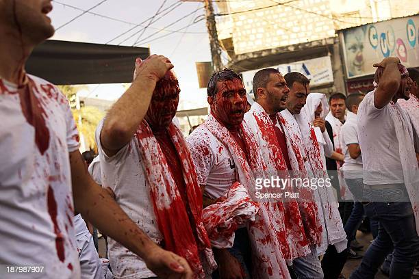 Shiite Muslim men bleed as they gash their foreheads with swords and beat themselves during a ceremony marking Ashura on November 14 2013 in Nabatieh...