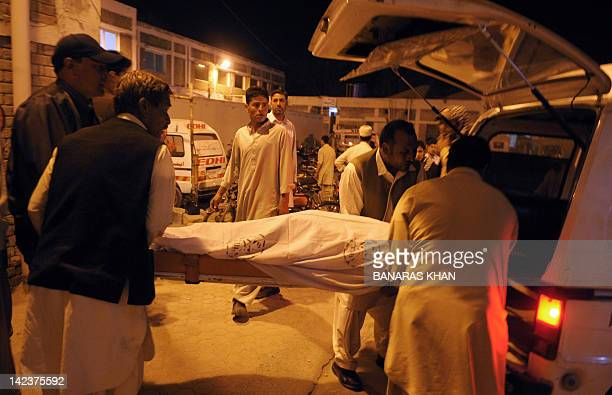 Shiite Muslim men place in an ambulance the body of a victim allegedly killed in a sectarian attack by gunmen in Quetta on April 3, 2012. Reports of...