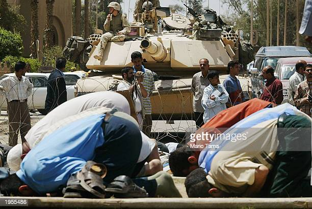 Shiite Muslim men pray in front of an American tank outside the Palestine Hotel April 28 2003 in Baghdad Iraq The prayer followed a protest for a...