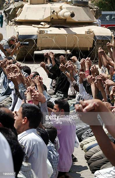 Shiite Muslim men pray in front of an American tank outside the Palestine Hotel April 28 2003 in Baghdad Iraq Several hundred Shiite Muslims...