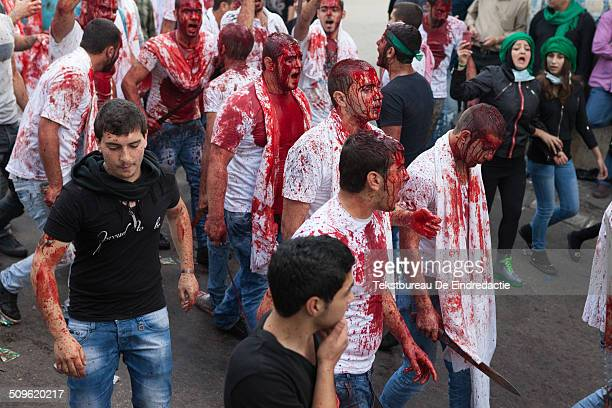 Shiite muslim men with selfinflicted headwounds covered in their own blood selfflagellating and marching through the streets of Nabatieh Lebanon...