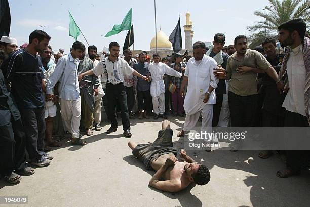 Shiite Muslim pilgrim crawls on his back around the holy mosques of Imam Hussein and Imam Abbas April 22 2003 in Karbala Iraq Iraqi Shiite Muslims...